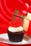 与一个红色重点的杯形蛋糕在配件箱的顶层和礼品在红色缎 库存图片
