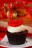 与一个红色重点的杯形蛋糕在配件箱的顶层和礼品在红色缎 库存照片