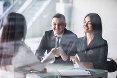 与一个经纪的愉快的年轻夫妇会议在她的倾斜在书桌的办公室握手,看法从女性代理tho的后面 免版税库存照片