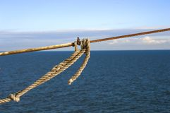 与一个结的船绳索在蓝色海背景 图库摄影