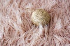 与一个绳索球的圣诞装饰在桃红色头发背景 库存图片