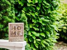 与一个绿色庭院的家庭标志在背景中 免版税库存图片