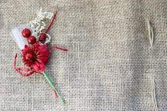 与一个绿色词根的一棵美丽的红色人造花在一块棕色老亚麻布的纹理,与粗砺的亚麻制自然材料 免版税库存照片