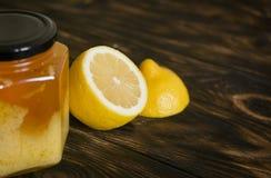 与一个罐头的柠檬在黑褐色背景的蜂蜜 库存图片