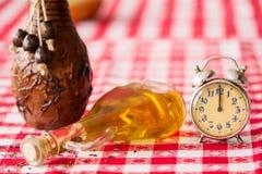 与一个老模式时钟和一个瓶的美好的安排油 库存照片