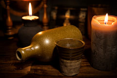 与一个老瓶、杯子和蜡烛的中世纪背景 免版税库存照片