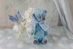 与一个花瓶的蓝色玩具熊有花的 免版税库存照片