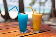 与一个蓝色和橙色鸡尾酒立场的两块玻璃在太阳的光芒的下一张木桌上 库存照片