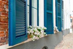 与一个蓝色太阳窗帘的窗口 免版税库存照片