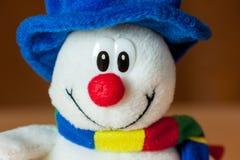 与一个蓝色帽子和一条五颜六色的围巾的一个逗人喜爱的矮小的软的雪人 库存图片