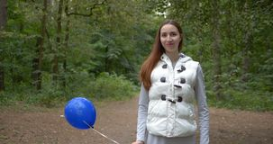 与一个蓝色气球的愉快的女孩身分和微笑在木头在slo mo 股票视频