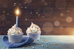 与一个蓝色蜡烛的杯形蛋糕 免版税库存图片