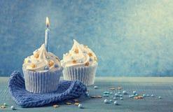 与一个蓝色蜡烛的杯形蛋糕 免版税库存照片