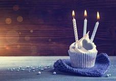 与一个蓝色蜡烛的杯形蛋糕 图库摄影