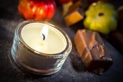 与一个蜡烛、巧克力和南瓜的万圣夜装饰在板岩 图库摄影