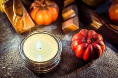 与一个蜡烛光、巧克力和南瓜的万圣夜装饰在板岩 库存照片