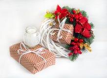 与一个蜡烛和礼物盒的圣诞节花圈 免版税库存照片