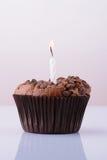 与一个蜡烛的巧克力杯形蛋糕在白色背景 免版税库存图片