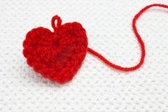 与一个螺纹圈的大红色钩针编织手工制造心脏在白色钩针编织背景 浪漫圣诞节或情人节概念 库存照片