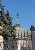 与一个行星和一只鸟的美好的雕塑在手中在一个古色古香的大厦的圆顶在篱芭后的衬托 免版税库存照片