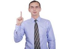 与一个被举的手指的商人。 库存图片