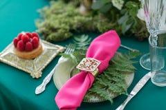 与一个被仿造的夹子的桃红色餐巾 制表设置 婚礼装饰在一对爱恋的夫妇的不可思议的森林里 桃红色和绿色 免版税库存照片