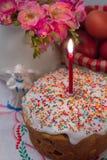 与一个被点燃的蜡烛、花、鸡蛋和天使小雕象的复活节蛋糕 免版税库存图片