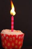 与一个被点燃的蜡烛的杯形蛋糕 库存图片