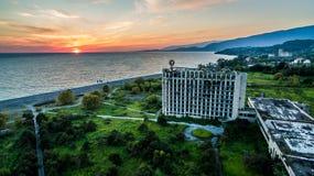 与一个被破坏的大厦的海景在明亮的日落的背景中 免版税库存图片