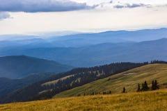 与一个谷的美好的山风景在C的多云天空下 库存图片