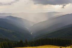 与一个谷的美好的山风景在C的多云天空下 免版税库存照片
