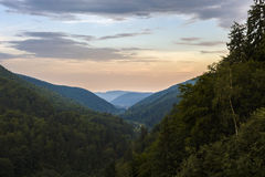与一个谷的美好的山风景在C的多云天空下 免版税库存图片
