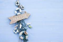 与一个路标的蓝色背景对海边 免版税库存图片