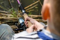 与一个转动的卷轴的年轻男孩渔 免版税图库摄影