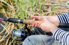 与一个转动的卷轴的年轻男孩渔 库存图片