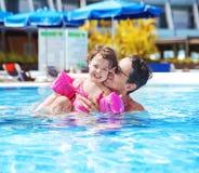与一个逗人喜爱的女儿的英俊的爸爸游泳 免版税库存图片