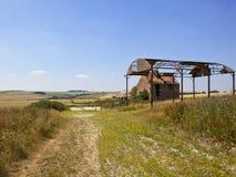 与一个遗弃农舍和谷仓的补缀品英国风景 免版税库存图片