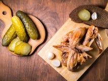 与一个酥脆外壳的烤鸡在一张点心桌上说谎用酱瓜,面包 免版税库存照片