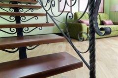 与一个金属黑楼梯的内部与木步和一个绿色沙发在客厅 库存照片