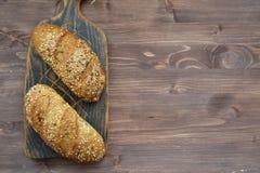 与一个金黄外壳的两个新近地被烘烤的嘎吱咬嚼的小圆面包在木背景的木切板和拷贝空间 库存图片