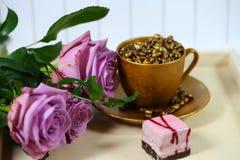 与一个金黄咖啡杯的3朵玫瑰 免版税库存图片