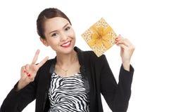 与一个金黄礼物盒的亚洲女商人展示胜利标志 图库摄影