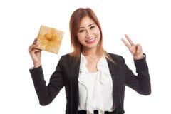 与一个金黄礼物盒的亚洲女商人展示胜利标志 库存图片