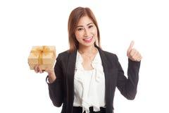 与一个金黄礼物盒的亚洲女商人赞许 图库摄影