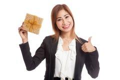 与一个金黄礼物盒的年轻亚洲女商人赞许 免版税库存图片