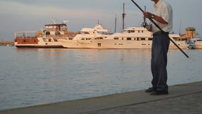 与一个钓鱼竿身分的人钓鱼在美丽的白色游艇背景的码头  渔夫转动 股票视频