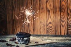 与一个闪烁发光物的巧克力杯形蛋糕在木背景 库存照片