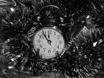 与一个闹钟的圣诞节闪亮金属片在一个黑白图象 免版税库存照片