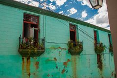 与一个阳台的老绿色大厦在城市街道上 圣地亚哥,古巴 库存图片