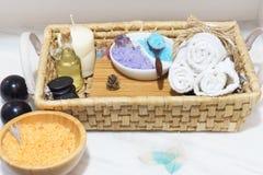 与一个集合的柳条筐温泉治疗的,五颜六色的盐、芳香油、石头、蜡烛和软的毛巾,在白色桌双旁边 库存图片